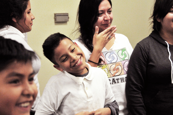 """Victor Perez, center, and mentor Anna Camberos smile as the next round of the the """"Titanic"""" friendship game is called out at the Silver Star Resource Center in Salinas."""