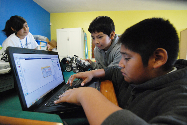 Partners Brandon Medina, center, and Victor Perez work on a programming solution.