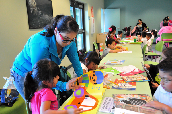 Tutor Elizabeth Pacheco has her hands full with different homework assignments at the Cesar Chavez Library's homework center in Salinas.