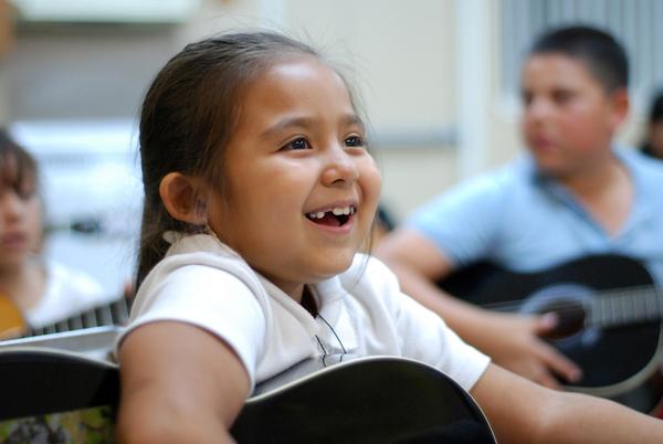 Liz Santoyo, 7, really enjoys Felix Miranda's open guitar class at CHISPA's Roosevelt Townhomes in Salinas.
